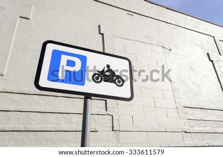 Road sign for parking motorbikes only, against a white wall  in the background England UK.