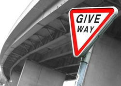 Road sign Give Way. British road sign Give Way opposite the motorway bridge by rainy day