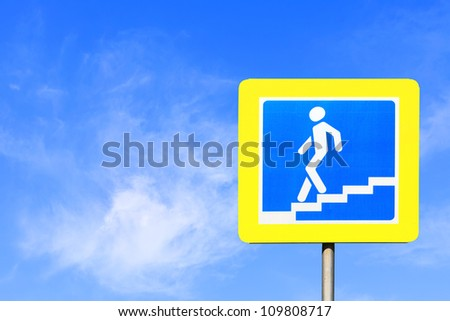Road sign of a pedestrian underpass against bright blue sky - stock photo