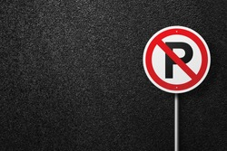 Road sign of the circular shape on a background of asphalt. No parking. The texture of the tarmac, top view.