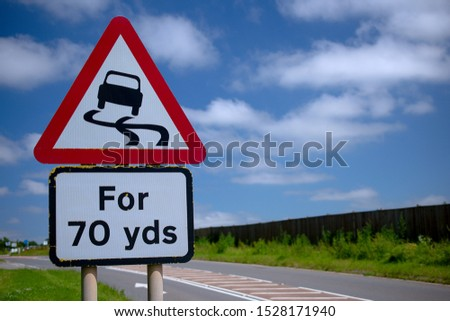 Road sign slippery when wet for 70 yards. blue cloudy sky