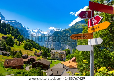 Road sign with arrows for hiking and biking tourist trails pointing fork in the road from village Wengen to Lauterbrunnen, Bernese Oberland, Switzerland. The Jungfrau is visible in the background