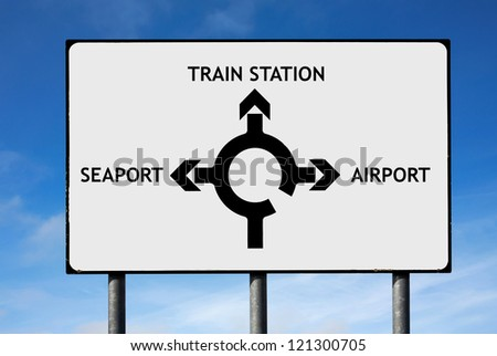 Road sign with roundabout directions pointing towards airport train station and seaport