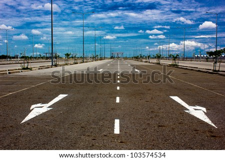 road signs arrows on asphalted surface - stock photo