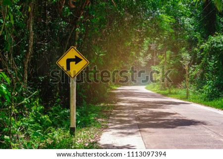 Road signs, indicating right turn on curve road. Turning right. Signal for safety or caution. Traffic warning sign for safe drive on empty curved road or path. Driving on forest road. Safety concept.