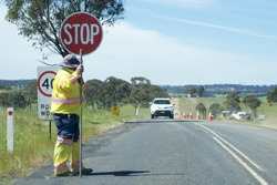 Road Stop sign being held by a worker.