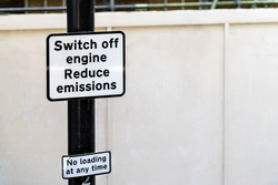 Road street sign for switch off engine to reduce emissions and no loading at any time in London, United Kingdom