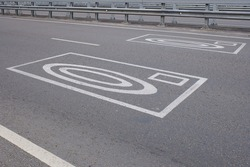 Road surface marking conveying information about red-light safety cameras.