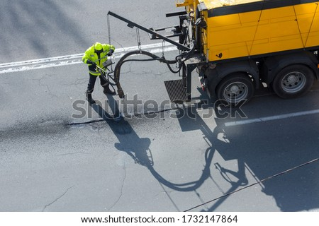 Road surface restoration work. The worker performs on road patcher work on the repair of cracks by filling and sealing with coated by bitumen emulsion and dry aggregate in the asphalt surface. Foto stock ©