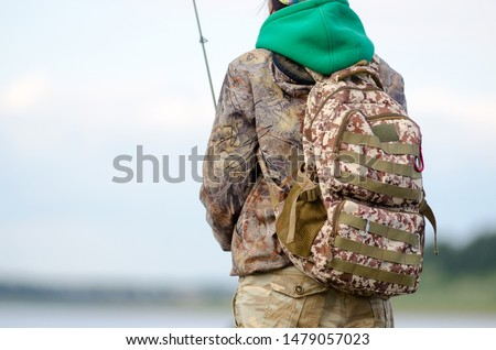 Road tactical backpack coloring worn on the back of the Yakut girls-tourist angler catches a fish in the hat on the Bank of the Vilyui river on the background of sky and clouds and fir taiga. #1479057023