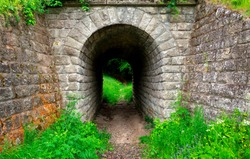 road through a stone tunnel leading to the forest