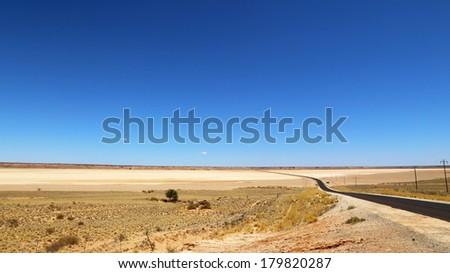 Road through arid landscape, Kalahari, South Africa