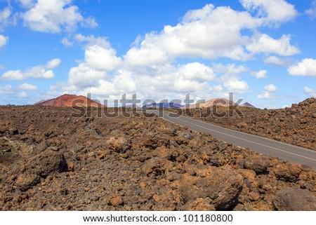 Road through lava rocks and volcanic mountains. Los Hervideros. Lanzarote