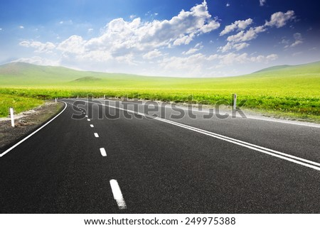 Road through meadow with cloud and sky background  #249975388