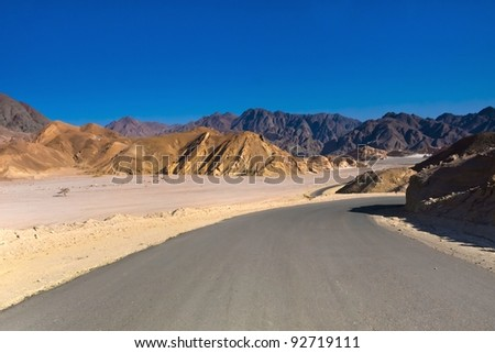 Road through the desert and sandy hills