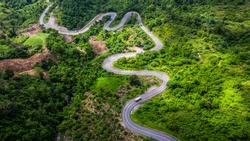 Road through the green forest, Aerial view car truck drive going through forest, Aerial top view forest, Texture of forest view from above, Ecosystem and healthy environment concept and background.