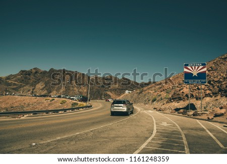 Road to Arizona with Arizona Flag Sign on a destructed rocks at a toe of a rocky mountain range. The cracked asphalt road with road lines and clear blue sky.  Vintage scene is presented