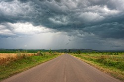Road to dramatic storm scene with rain at the horizon. Dark sky and dramatic black cloud.