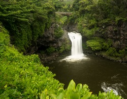 Road to Hana continues over bridge over waterfall into Seven Sacred Pools at state park