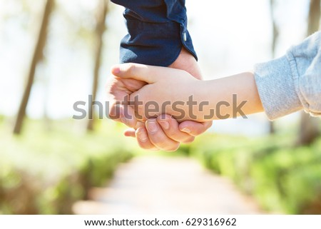 Road to life. Hands. Father\'s and his son hands. Dad leading son over summer nature outdoor. Male and children hands closep. Family, trust, protecting, care, parenting concept.