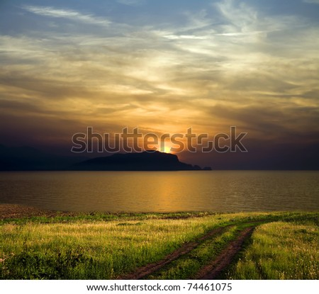 Road to sea. Sunset above mountain. Beautiful autumn landscape.