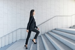 Road to success concept with businesswoman climbing the stairs in modern loft style hall
