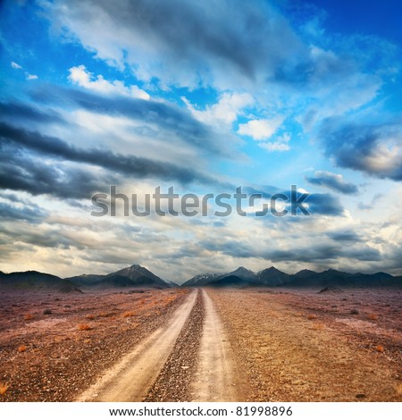 Road to the mountains through the desert at sky with clouds