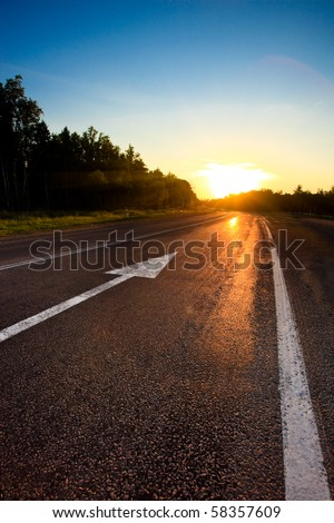 road to the sunset with arrow on asphalt