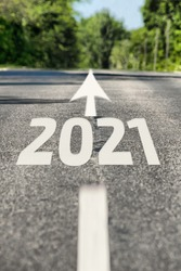 Road to 2021 year. Asphalt road with road markings and 2021 sign. Direction to the future 2021 year