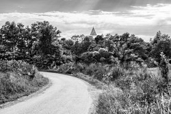 Road towards Somartin village with the tower of the fortified evangelical church seen beyound trees in Somartin village, Sibiu county, Transylvania, Romania in black and white