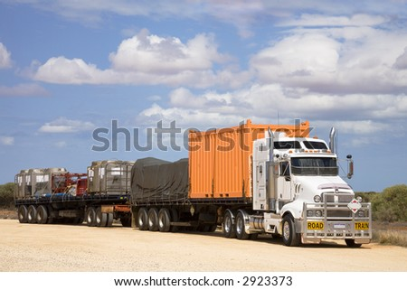 Road train in a rest area, with a load of shipping containers of various kinds, and something covered with a tarpaulin