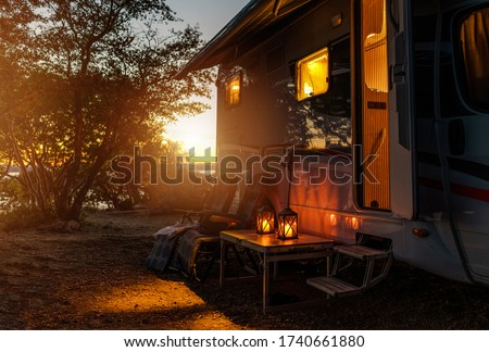 Road Trip Adventures. Calm Warm Night on a Camping. Camper Van, Outdoor Chairs and Romantic Light From Lanterns. Vacation in Recreational Vehicle. Stock foto ©