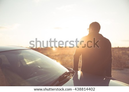 Road trip break after long drive.Young stylish man enjoys sunset.Young man fascinated by illuminated nature, escape from everyday job problems. Open field delight of natural beauty view.
