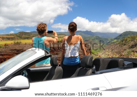 Road trip car people taking phone pictures of nature landscape on summer travel vacation. Tourists couple taking photos on Hawaii Kauai island, with smartphone camera app.