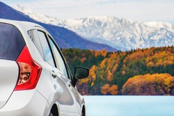 Road Trip Concept, Car Driving Travel in Fall and Autumn Season, Lake, beautiful Foliage and Mountains covered by Snow as background