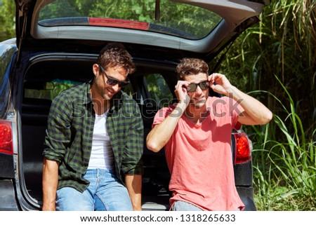 Road trip dudes adjusting sunglasses in back of car