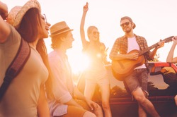 Road trip is fun. Group of young cheerful people dancing and playing guitar while enjoying their road trip in pick-up truck together