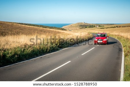 Road Trip; South Downs, England. A car travelling a winding road on the South Downs (East Sussex, England) with Belle Tout lighthouse and the English Channel in the distance. Deliberate motion blur.
