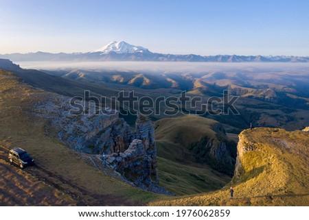 Road trip to Bermamyt plateau. Sunrise aerial view of car on the cliff and mount Elbrus. Karachay-Cherkessia, Caucasus, Russia.