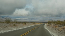 Road trip to Death Valley, driving auto in California, USA. Hitchhiking traveling in America. Highway, mountains and dry desert, arid climate wilderness. Passenger POV from car. Journey to Nevada.