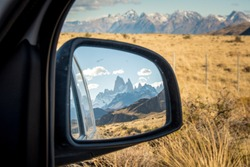 Road trip to National Park Los Glaciares in El Chalten, Chile: View on famous Mount Fitz Roy in Patagonia through reflection of side Mirror of camper van