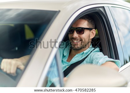 road trip, transport, travel and people concept - happy smiling man in sunglasses driving car #470582285