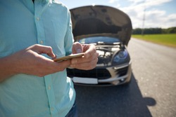 road trip, transport, travel, technology and people concept - close up of man with smartphone and broken car