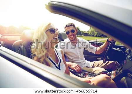 road trip, travel, dating, couple and people concept - happy man and woman driving in cabriolet car outdoors #466065914