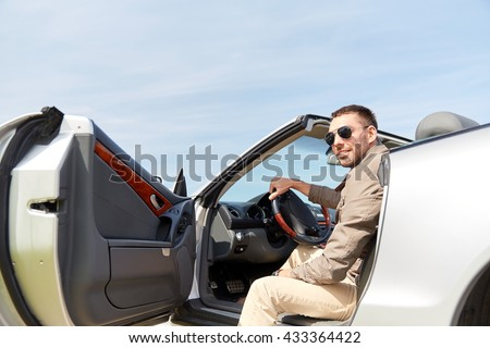 road trip, travel, transport, leisure and people concept - happy man opening door of cabriolet car outdoors #433364422