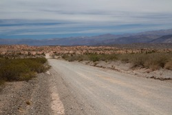 Road trip. Traveling along the dirt road across the arid desert, canyon and mountains.