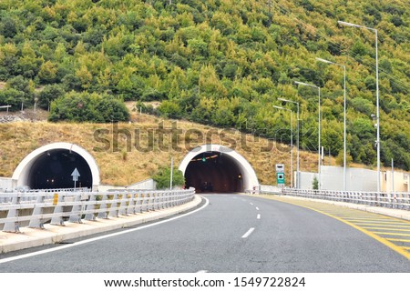 Road tunnel in mountains. Mountain road tunnel with luminous safety lights and yellow road line. Tunnel on the highway.  Automobile trip. Pathway with tunnel. Drive through the mountain #1549722824