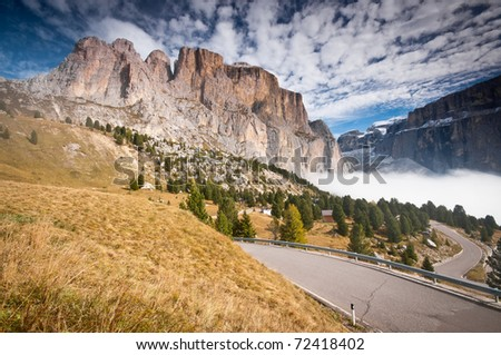 Road under the peaks in autumn Dolomites