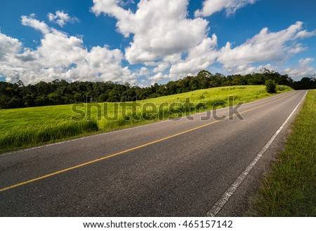 Road up hill with green grass field under white clouds and blue sky.