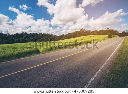 Road up hill with green grass under white clouds and blue sky.